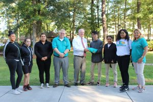 Early College students presenting polo shirt to president Findt