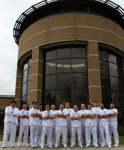 Male nursing students dressed in white and standing in front of the library