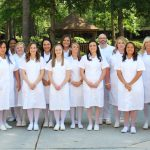 Associate degree nursing students dressed in white uniforms and standing in a row on campus
