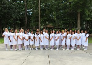 2018 practical nursing graduates standing on campus in nursing whites