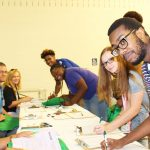 Students completing paperwork at table during orientation