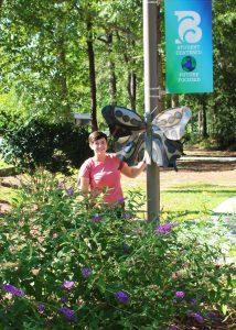 Savannah Schmidt Standing beside welding sculpture of butterfly