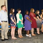 Students standing in a row waiting to receive recognition as members of Sigma Kappa Delta national English Honor Society