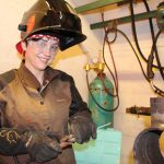 Photo of Savannah Schmidt dressed in welding gear