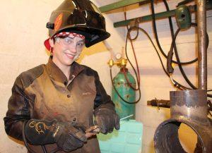 Photo of Savannah Schmidt dressed in welding gear